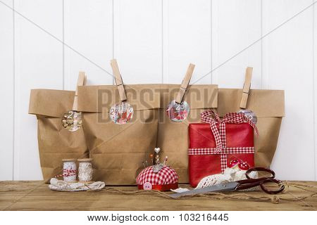 Crafted christmas presents wrapped in paper bags with wooden clips in red and white colors with sewing supplies.