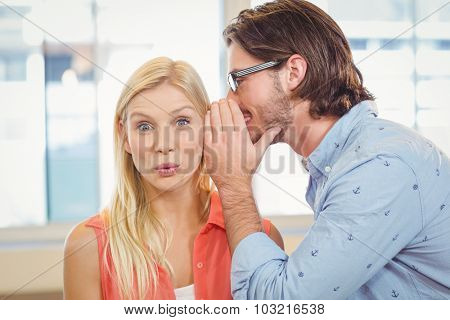 Businesswoman listening to rumor which male colleague is whispering into her ear