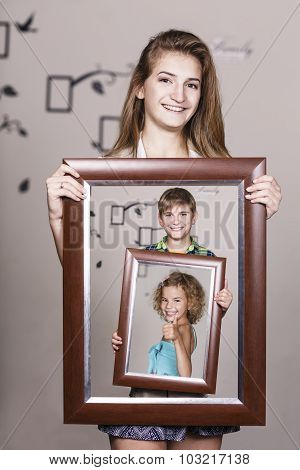 Adult sister holding portrait with her family