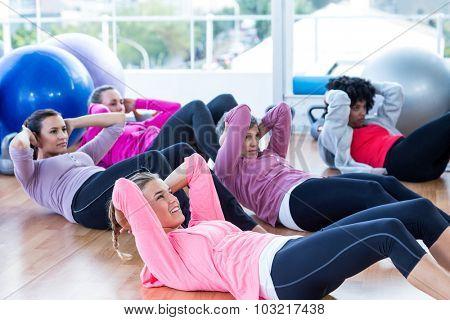 Sporty women doing sit ups on hardwood floor in fitness studio