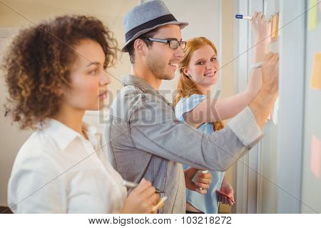 Portrait of smiling businesswoman writing on adhesive notes on glass wall during meeting in office