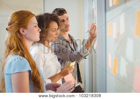Businessman writing on glass as female colleagues looking at it during meeting in office
