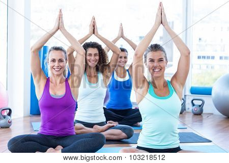 Portrait of cheerful women sitting on exercise mat with hands overhead in fitness studio