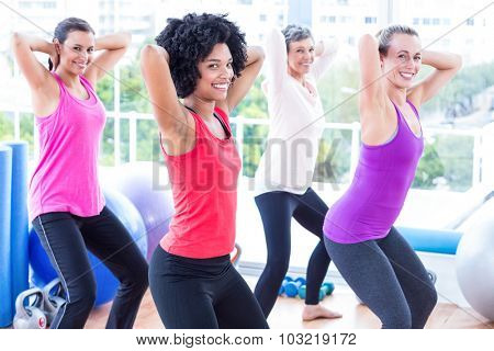 Portrait of smiling women exercising with hands behind head in fitness studio