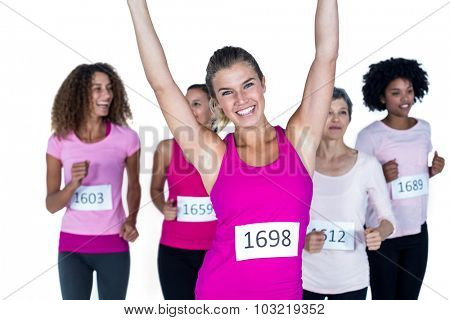 Portrait of smiling winner athlete with arms raised and others running against white background