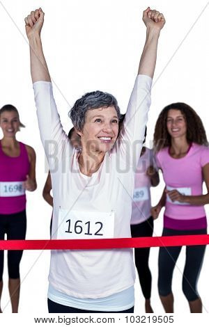 Happy winner athlete crossing finish line with arms raised against white background