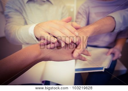 Close-up of business people with hand stack in meeting at creative office