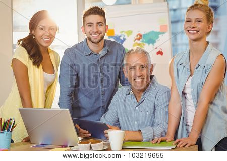 Portrait of happy business people using technologies in meeting room at creative office