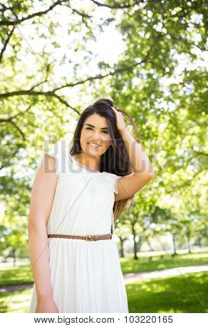 Portrait of pretty woman with hand in hair standing on grassland in park