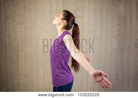 Side view of woman with arms outstretched and eyes closed while standing at home