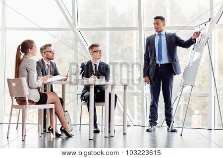 Successful businessman standing by whiteboard and explaining data to colleagues during presentation