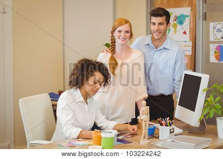 Portrait of smiling business people standing by colleague working at desk in office