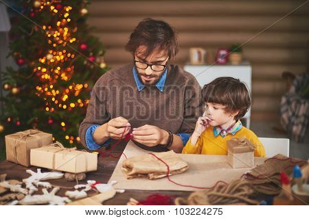 Young man preparing thread for tying xmas gifts with his son near by