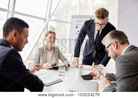 Two businessmen looking at data in cellphones with their colleagues near by