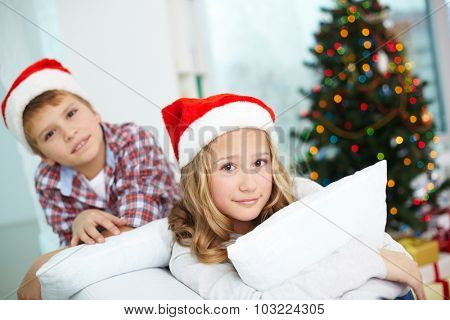 Adorable girl in Santa cap looking at camera with cute boy on background