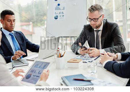 Businessmen using modern gadgets at meeting