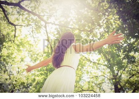 Low angle view of long hair woman with arms outstretched against trees
