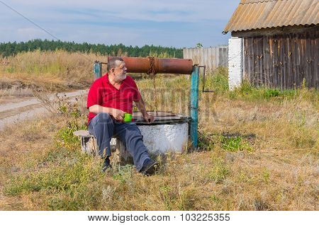 Bearded senior man sitting at country draw-well
