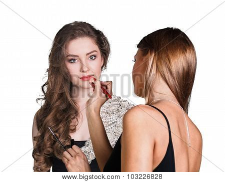 Make-up artist applying lip liner on model's lips