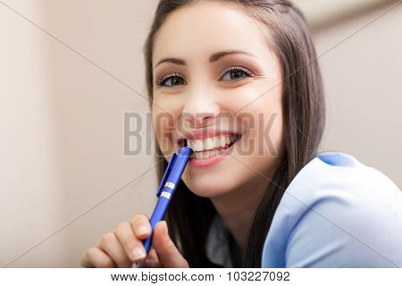 Beautiful young businesswoman holding a pen