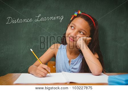 The word distance learning and cute pupil at desk against green chalkboard