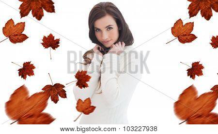 Brunette in white jumper smiling at camera against autumn leaves pattern