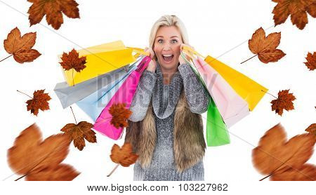 Blonde in winter clothes holding shopping bags against autumn leaves pattern