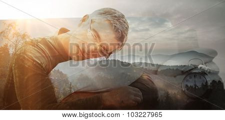 Man resting on cushion against trees and mountain range against cloudy sky