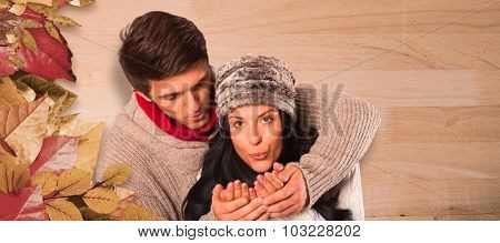Young couple blowing over hands against bleached wooden planks background
