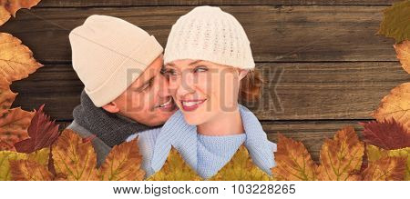 Casual couple in warm clothing against overhead of wooden planks