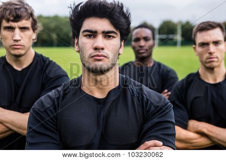 Rugby players scowling at camera at the park