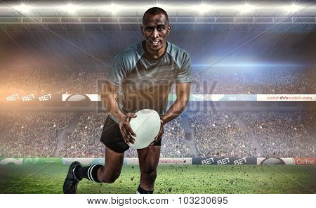 Portrait of determined sportsman running with rugby ball against rugby stadium