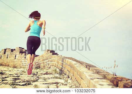 woman runner athlete running on trail at chinese great wall.