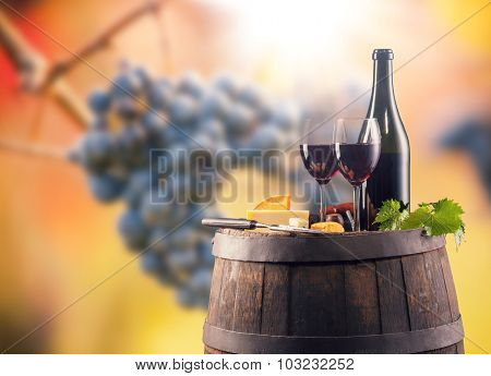 Red wine bottle and glass on wooden keg. WIne grapes on background