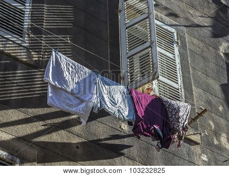 Woman With Scarf Pegs Out The Washing On A Washing Line In Front Of The Facade