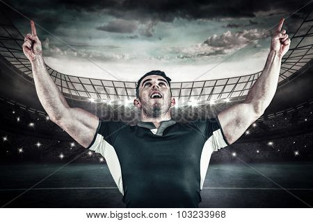Rugby player cheering and pointing against large football stadium under blue sky