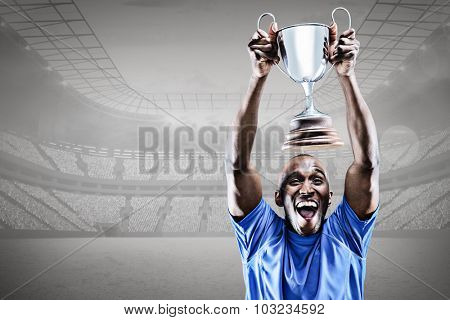 Happy athlete cheering while holding trophy against grey vignette