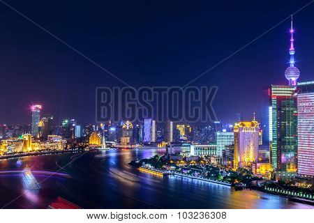 night scene of the city with a river around skyscrapers