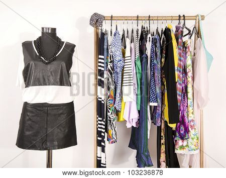 Dressing Closet With Colorful Clothes Arranged On Hangers And An Outfit On A Mannequin.