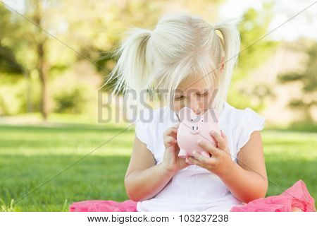 Cute Little Girl Having Fun with Her Piggy Bank Outside on the Grass.