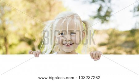 Cute Little Girl Outside Holding Edge of White Board with Room For Text.
