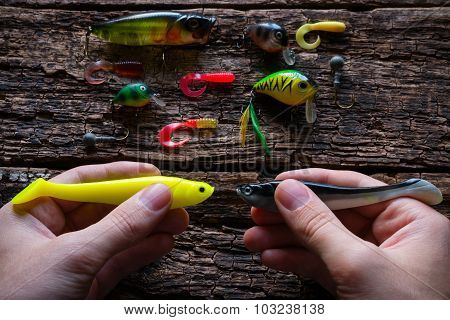 Man Holding Two Lures For Fishing With Spinning