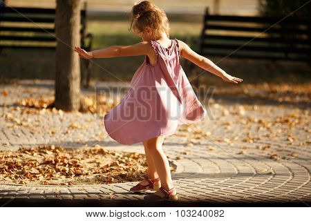 Full Length Portrait Of A Little Girl Dancing In The Park A Warm Autumn Evening. In Move