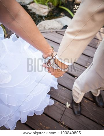 bride and groom hands handcuffed together at the wrists arm and legs only
