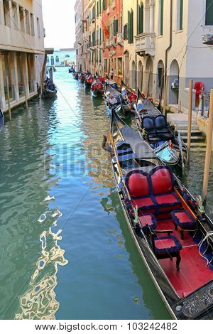 VENICE, ITALY - SEPTEMBER 2014 : Some Gondolier men sitting and resting in their Gondola boats on Venetian canals in Venice, Italy on September 14, 2014.