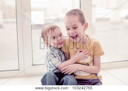 two boys laugh by playing