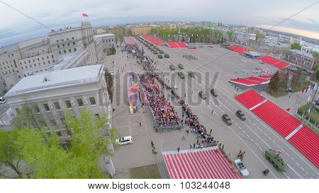 SAMARA - MAY 06, 2015: Military motorcade moves along square with empty tribunes and crowd of people at spring evening. Aerial view video frame