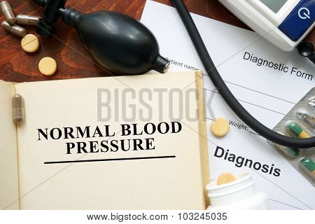 Normal blood pressure written on a book.