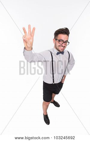 Handsome man showing three fingers in studio