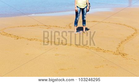 Woman standing in the heart drew on the sand on the seashore, Portugal